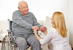 caregiver and elder man in a wheelchair holding hands