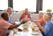 Senior men giving food to friends