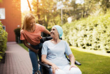 A woman with cancer is sitting in a wheelchair