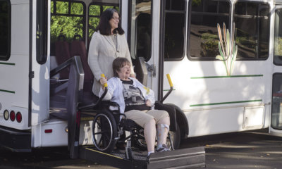 A woman in a wheelchair is helped off a van using a chair lift