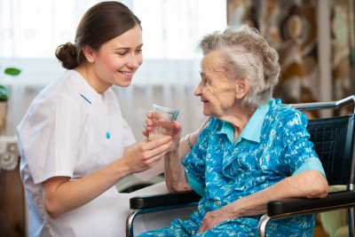 caregiver serving a glass of water for elder woman