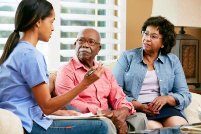 nurse and elderly couple talking